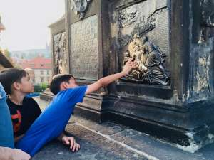 Touch the St John Statue on the Charles Bridge in Prague or good luck